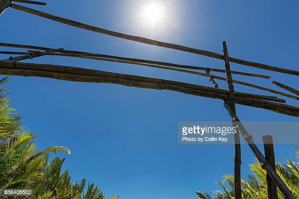 a very shaky bamboo bridge against the sun and a blue sky. - collin key stock-fotos und bilder
