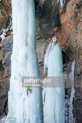 Very strong woman climbing on a frozen ice pillar.
