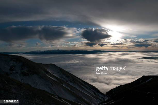 Very suggestive sunset seen from Campo Imperatore at 2115 metres above sea level. An expanse of clouds hides the city of L'Aquila, Italy, on November...