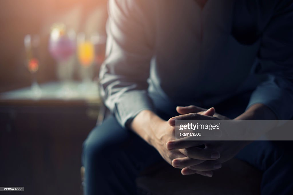 very Tired or stressed businessman hand touching head and sitting in front of cocktail and alcohol drink with darken mood and tone : Stockfoto