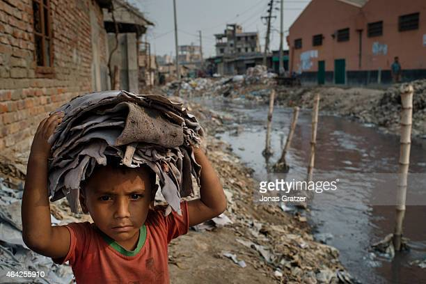A very young child laborer is carrying remnants of leather on his head from waste products that are worth billions per year from a wasteland full of...
