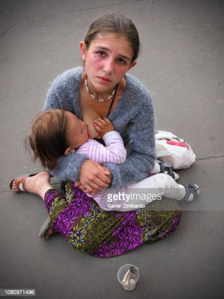 Very young woman breastfeeding small child and begging on June 17 2008 in Moscow Russia