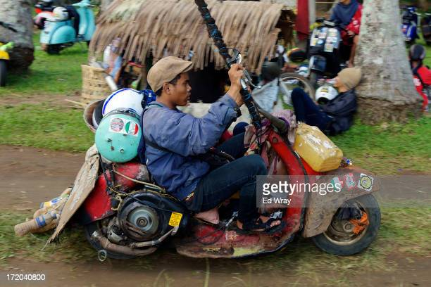 Vespa enthusiast arrives at a scooter festival in his extreme Vespa modification on June 30 2013 in Cibeureum about 100 km west of Jakarta Indonesia...