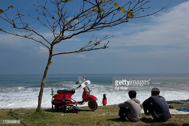 Vespa enthusiasts sit at the beach during a scooter festival on June 30 2013 in Cibeureum about 100 km west of Jakarta Indonesia Hundreds of Vespa...