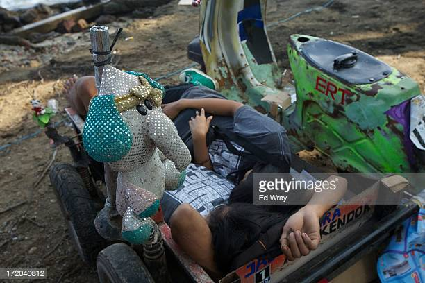 Vespa enthusiasts sleep in heavily modified scooters during a scooter festival on June 30 2013 in Cibeureum about 100 km west of Jakarta Indonesia...