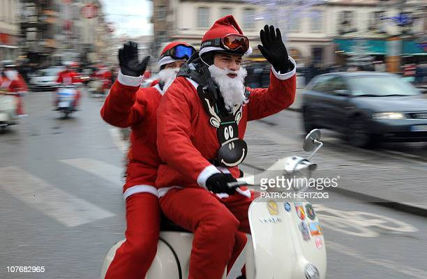 Vespa scooter driver and passenger dressed up as Santa Claus wave as they parade through the streets of Strasbourg on December 19 2010 Around 30...