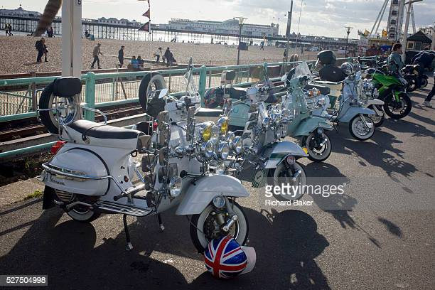 Vespa scooters on display on Brighton's seafront esplanade on Bank Holiday weekend Fitted to the frame of the bike are many headlights and mirrors...
