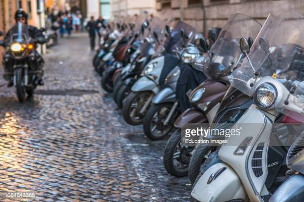 Vespas and other motorcycles on Rome cobbled streets, Lazio, Italy.