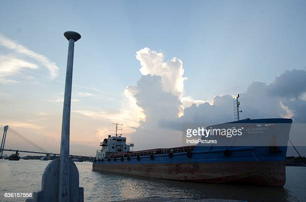 Vessels and Barges with Second Hooghly Bridge At Background Over Hooghly River At Sunset Kolkata West Bengal
