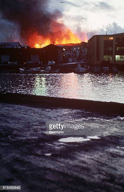 1/24/1973 Vestmannaeyjar off Iceland View from the sea with the harbor and Fish Industry building foreground as crater in background is in full blast