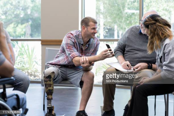vet with prosthesis shows photo on phone to group members - amputee stock pictures, royalty-free photos & images