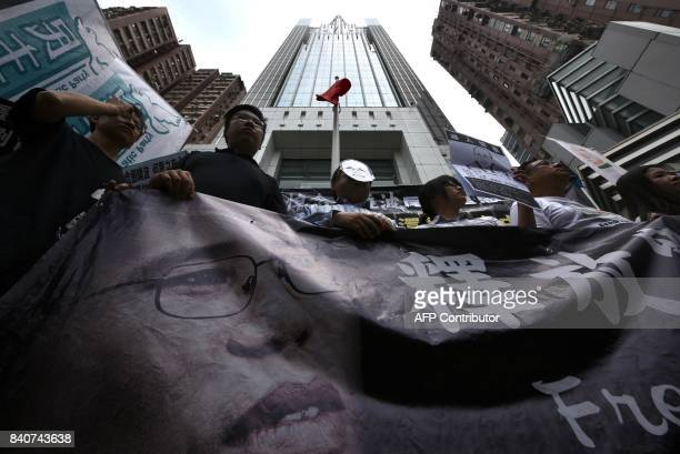 Veteran activist and former lawmaker Albert Ho wears a mask depicting Liu Xia wife of the late Chinese Nobel laureate Liu Xiaobo during a protest in...