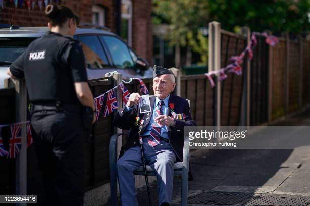 WWII veteran Bernard Morgan aged 96 shows a police officer a photograph of himself as a young man as he takes part in the VE day street party in his...