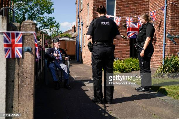 WWII veteran Bernard Morgan aged 96 talks to police officers as he takes part in the VE day street party in his garden on May 08 2020 in Crewe United...