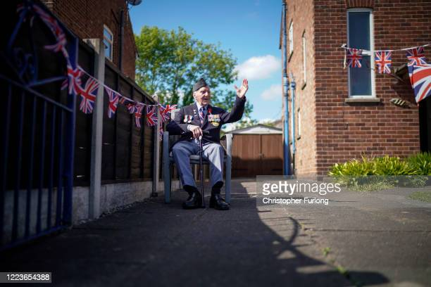 WWII veteran Bernard Morgan aged 96 waves to well wishers as he takes part in the VE day street party in his garden on May 08 2020 in Crewe United...