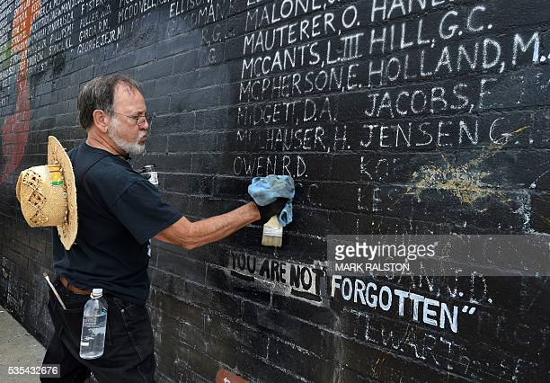 Veteran Charle Saulenas cleans a Veterans Memorial containing the names of 2273 unaccounted and missing in action Vietnam war soldiers after vandals...