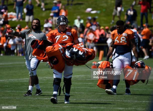 Veteran Denver Broncos offensive guard Billy Turner #77 left guides Denver Broncos rookie offensive tackle Garett Bolles and Denver Broncos rookie...