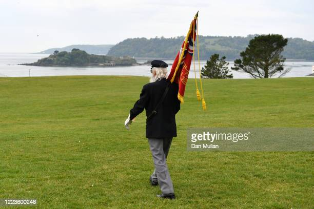 A veteran flag bearer makes leaves the Naval War Memorial following the playing of the last post on May 08 2020 in Plymouth United KingdomThe UK...