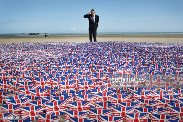 WW2 veteran Fred Holborn from the Fleet Air Arm salutes as he looks at British Legion Union flags carrying thank you messages planted in the sand on...