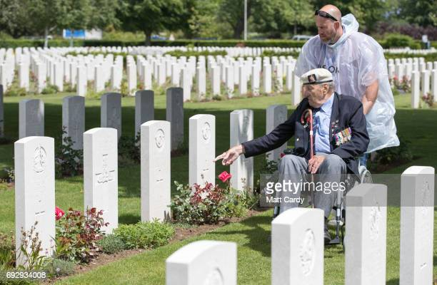 Veteran Harry Card who served on HMS Swift on DDay looks at the headstones with his son Lee Card at Bayeux Cemetery as part of the commemorations of...