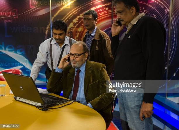 """Veteran Indian journalist Saeed Naqvi, seated, speaks on the telephone March 8, 2014 as he prepares to record his foreign affairs talk show """"Wide..."""