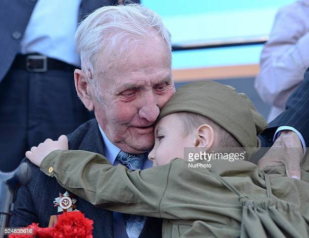 Veteran is getting a hug from a young local boy after he received flowers from him, during 'Immortal Regiment' march, as thusands take part in a walk...