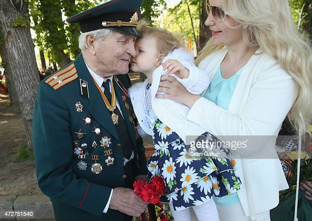 Veteran Ivan Masyeyevich Kazantsev who fought in World War II with the Soviet Red Army against the Japanese in northern China gets a snuggle from a...