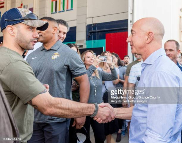 A veteran left shakes the hand of Jeff Bezos founder and CEO of Amazon after he made a surprise appearance during a Amazon Veterans Day celebration...