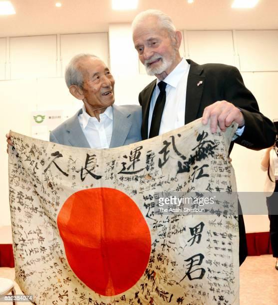 US WWII veteran Marvin Strombo returns the Japanese flag to Tatsuya Yasue during a ceremony on August 15 2017 in Higashishirakawa Gifu Japan The flag...