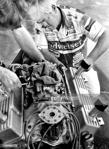 Veteran NASCAR driver and car owner Junior Johnson works on an engine in the speedway garage prior to the running of the 1985 Daytona 500 stock car...