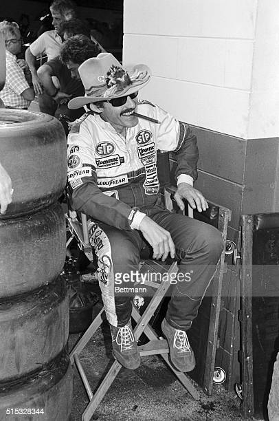 Veteran NASCAR driver Richard Petty with his trademark hat sunglasses and cigar relaxes on a director's chair in the garage area 2/15 Petty holds...