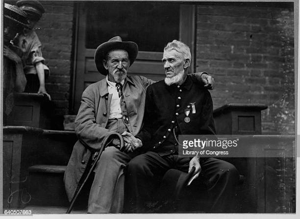 A veteran of the Union Army shakes hands with a Confederate veteran at the Gettysburg celebration Pennsylvania ca 1913
