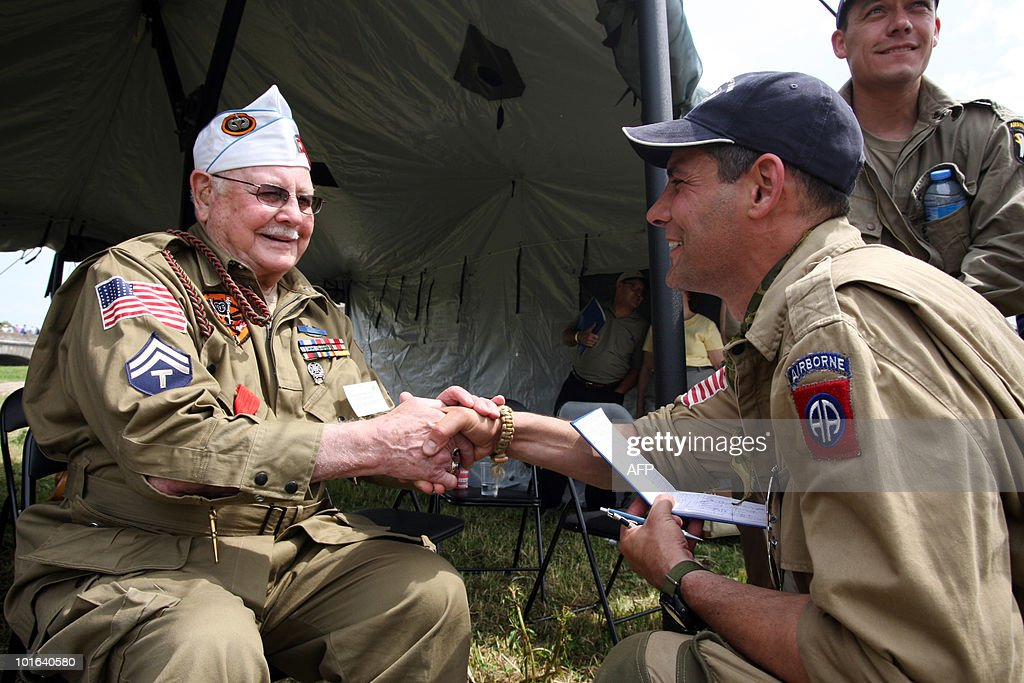 A US veteran of the World War II (L) shakes hands with a man on June 5, 2010 near Sainte-Mere-Eglise, during the D-Day celebrations to mark the 66th anniversary of the June 6, 1944 allied landings in France. AFP PHOTO KENZO