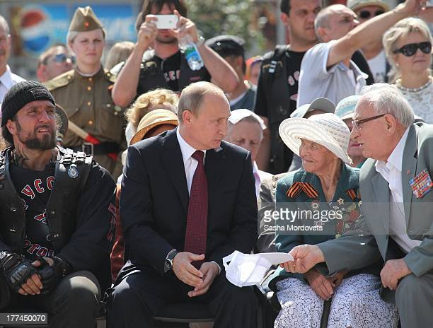 WWII veteran offers a hat to Russian President Vladimir Putin as Night Wolves Moscow Bikers club leader Alexander 'Khirurg' Zaldostanov looks on...