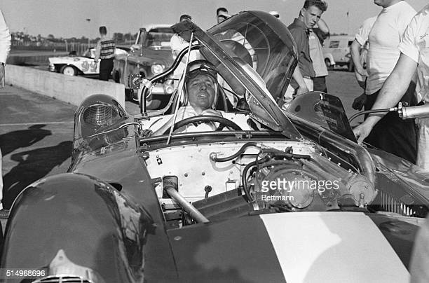 Veteran race car driver Marshall Teague tightens his helmet as he settles himself in the cockpit of this car at Daytona Beach on February 10 On...
