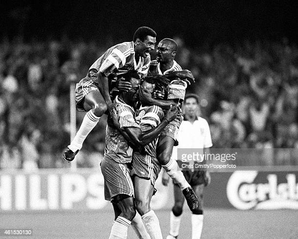 Veteran striker Roger Milla joins in the celebrations after Cameroon score against England during the FIFA World Cup quarterfinal match between...
