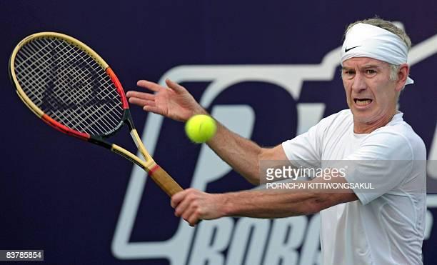 Veteran US tennis player John McEnroe hits a return during an exhibition match against Swedish tennis legend Bjorn Borg in Bangkok on November 22...