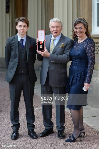 Veteran war photographer Sir Don McCullin with his son Max and wife Catherine after he was knighted by the Prince of Wales during an investiture...