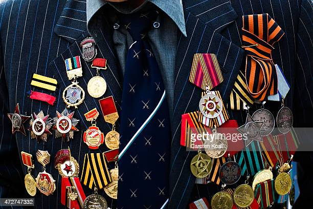 A veteran wears several medals on his dress as other people gather to commemorate on Victory Day when Nazi Germany surrendered to the Soviet Union at...