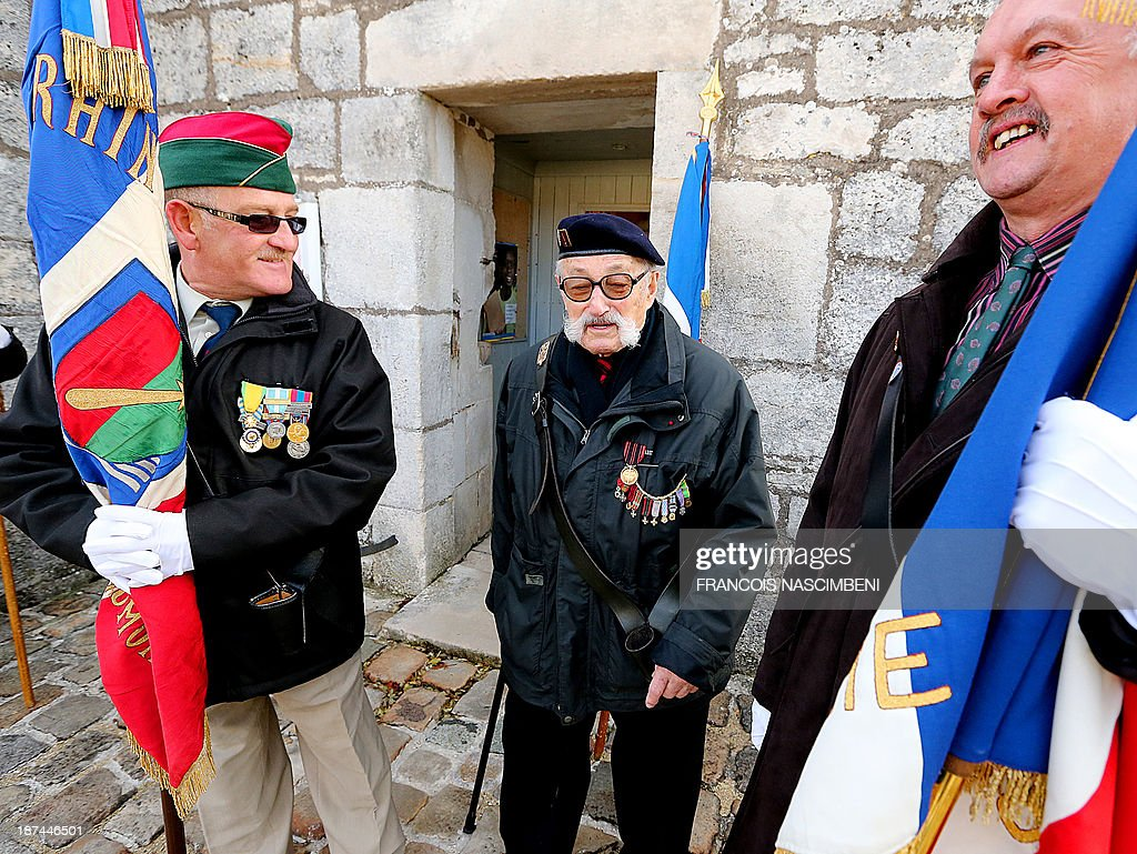 Veterans and flag bearers attend on November 9, 2013 at the tomb of late French President, General Charles De Gaulle, a ceremony marking the 43rd anniversary of his death at a cemetery in Colombey-les-Deux-Eglises.