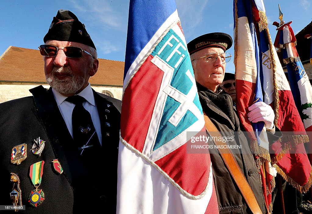 Veterans and flag bearers pay their respect on November 9, 2013 at the tomb of late French President, General Charles De Gaulle, during a ceremony marking the 43rd anniversary of his death at a cemetery in Colombey-les-Deux-Eglises.