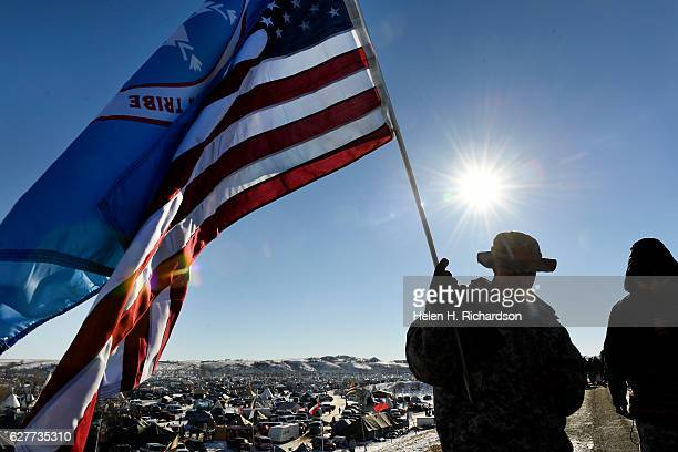 Veterans and native americans hold flags on the road near Oceti Sakowin Camp on the edge of the Standing Rock Sioux Reservation on December 4, 2016...