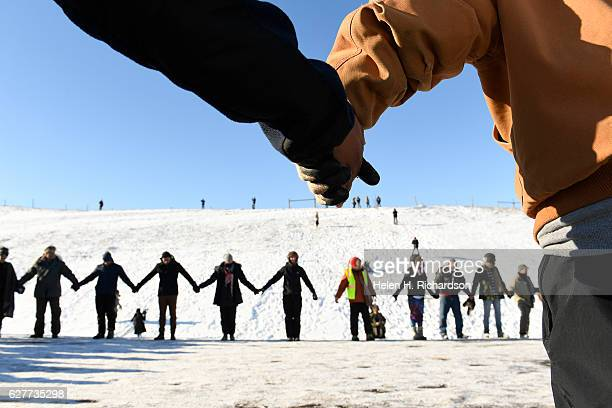 US veterans and native americans hold hands in prayer and solidarity on the road near Oceti Sakowin Camp on the edge of the Standing Rock Sioux...