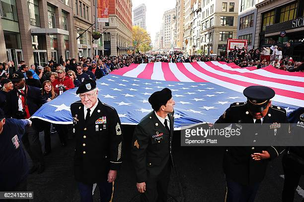 Veterans and others carry a large American Flag while marching in the nation's largest Veterans Day Parade in New York City on November 11 2016 in...