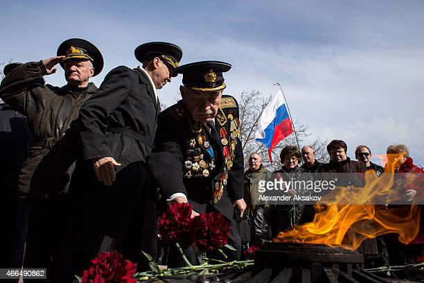 Veterans bring flowers to the eternal flame on the memorial of the heroic defense of Sevastopol as Crimeans celebrate the first anniversary of the...
