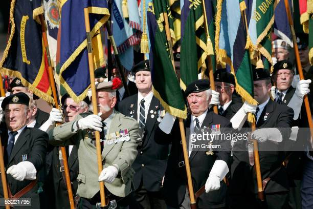 Veterans carrying regimental colours parade along the Mall after attending the service to commemorate the end of World War II on July 10 2005 in...
