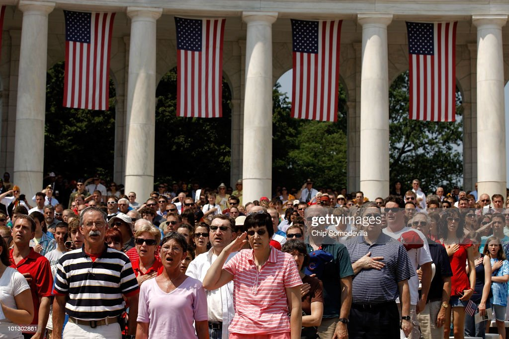 Veterans, civilians and their families salute and hold their hands over their hearts while the National Anthem is played during Memorial Day ceremonies at Arlington National Cemetery May 31, 2010 in Arlington, Virginia. This is the 142nd Memorial Day observance at the cemetery.