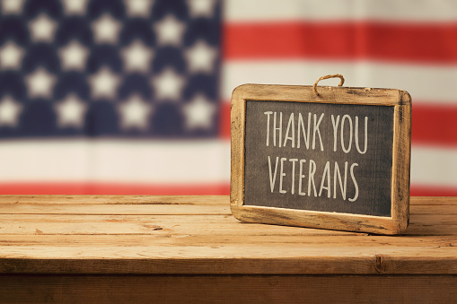 Veterans day background with chalkboard on wooden table and USA flag 868015278