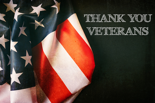 Veterans day background with text and USA flag 1054999012