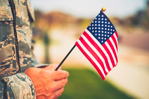 Veteran's Day in America. Soldier with American Flag 849066672